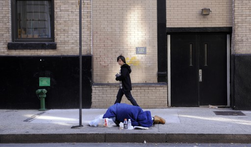 File: A woman walks past a man sleeping on a street in New York, EPA/JUSTIN LANE