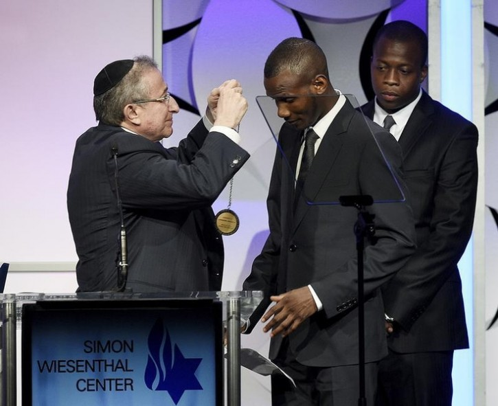 Lassana Bathily (C), a Muslim immigrant form Mali who hid Jewish shoppers at a kosher market in Paris during a hostage situation with a terrorist, receives Medal of Honor from Rabbi Marvin Heir (L) as he is honored by the Simon Wiesenthal Center in Beverly Hills, California March 24, 2015. REUTERS/Kevork Djansezian