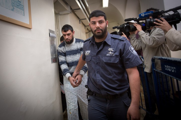 Police escort East Jerusalem resident Khaled Kutina to his hearing at the Magistrate's Court in Jerusalem. Kutina rammed his car into a bus stop in the Jerusalem neighborhood of French Hill last night, killing a young Israeli man and injuring a woman. Police are investigating the possibility that the incident may have been a terrorist attack. April 16, 2015. Photo by Miriam Alster/FLASH90
