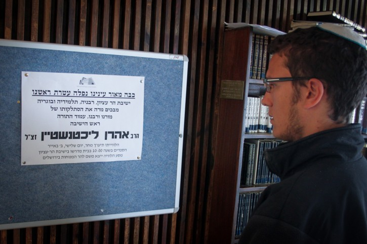 A Jewish student from the Har Etzion yeshiva looks at a poster announcing the death of Rabbi Aharon Lichtenstein, head of the Har Etzion yeshiva, on April 20, 2015.  Flash90