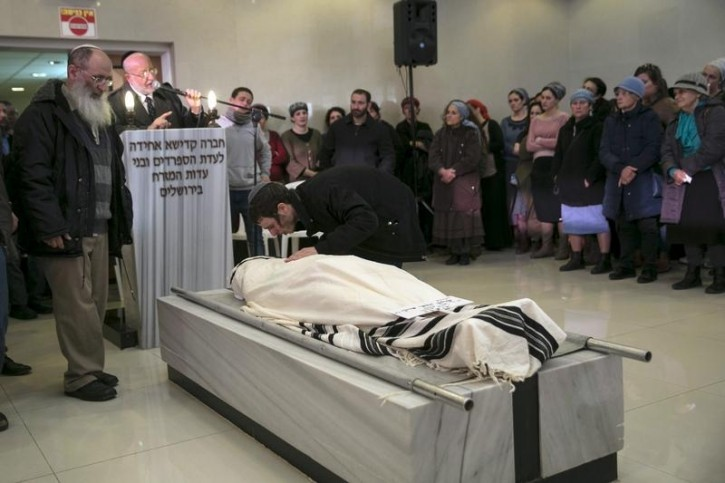 Rabbi Uri Sherki (L) stands next to the body of his son Shalom Yohai Sherki, 25, as his other son Yair mourns, during the funeral in Jerusalem April 16, 2015.REUTERS
