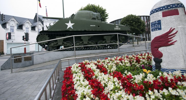 A WWII tank and a marker are surrounded by flowers in the town center of Bastogne, Belgium on Saturday, Aug. 29, 2015. A memorial was held in the town on Saturday for Augusta Chiwy, 94, a Belgian nurse who helped save hundreds of American soldiers during the Battle of the Bulge at the end of World War II. (AP Photo/Virginia Mayo)