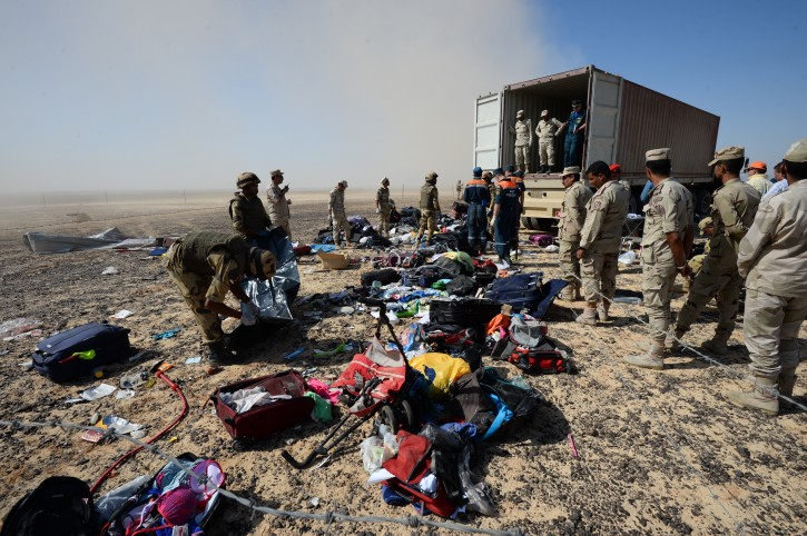 FILE - In this Monday, Nov. 2, 2015 file photo provided by the Russian Ministry for Emergency Situations, Egyptian soldiers collect personal belongings of plane crash victims at the crash site of a passenger plane bound for St. Petersburg in Russia that crashed in Hassana, Egypt's Sinai Peninsula.  (Russian Ministry for Emergency Situations via AP, File)
