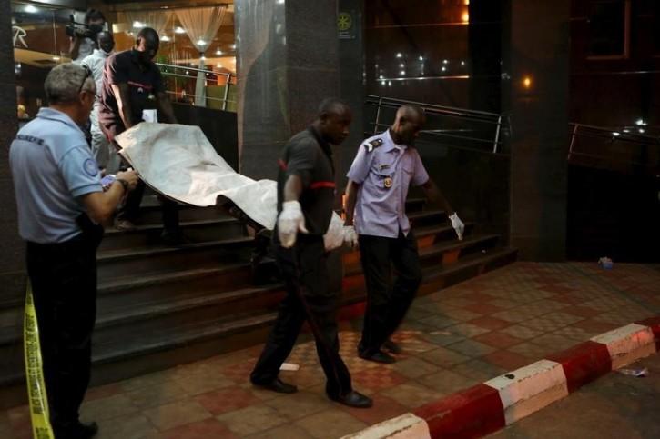 Malian officials carry a corpse outside the Radisson hotel in Bamako, Mali, November 20, 2015. Reuters