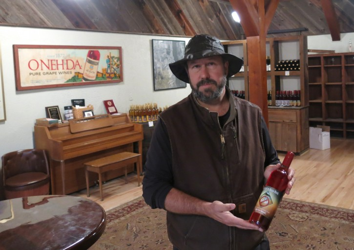 """In this photo taken on Thursday, Oct. 22, 2015, Will Ouweleen, owner of Eagle Crest and O-Neh-Da wineries, poses with a bottle of """"No Trash! Di Blasio Blush"""" in Conesus, N.Y.  Ouweleen rolled out the new label to protest a New York City contract to ship trash by train to a large landfill in the Finger Lakes. Ouweleen and other opponents of the Seneca Meadows Landfill say the facility is an eyesore that's not good for tourism in the Finger Lakes wine region. (AP Photo/Mary Esch)"""