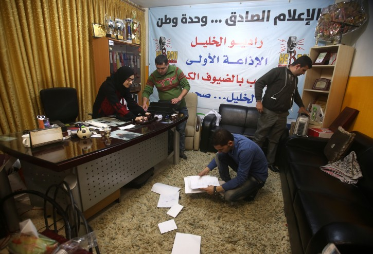Palestinian journalists inspect the damage of the Al-Khalil radio station in the West Bank city of Hebron, 21 November 2015. Israeli forces on 03 November raided the radio station in the West Bank city of Hebron and ordered it shut down for six months, Palestinian officials said. Journalist Amjad Shawar, the director of the station, Al-Khalil 90.4 FM, said a large army unit marched into the station's office in the Palestinian-controlled section of Hebron and seized equipment before handing the staff a closing order. EPA/ABED AL HASHLAMOUN
