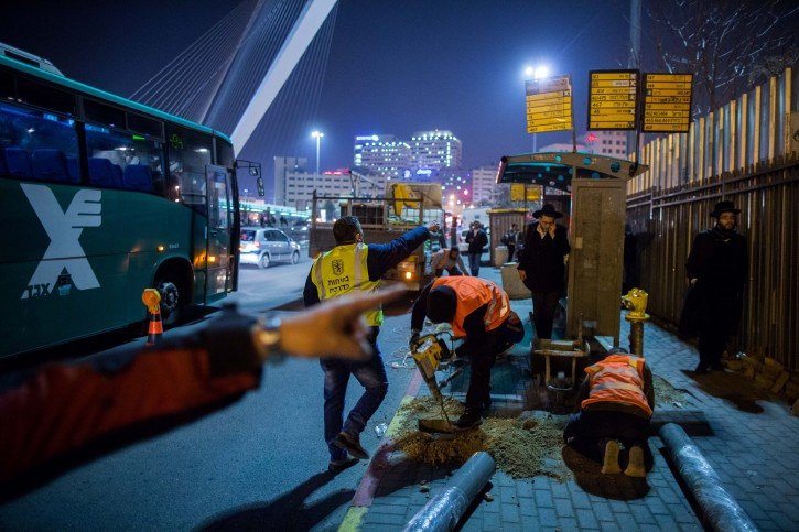 Israeli and palestinian labour workers palce barriers at a bus stop where a terror attack took place last week in Jerusalem on December 20, 2015. The Jerusalem municipality started on Sunday night to place barriers at bus stops around the city as protection against terrorism. Photo by Yonatan Sindel/Flash90