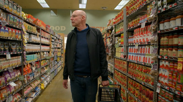 """In this undated photo provided by Kikim Media, author and host Michael Pollan educates viewers how to shop the outer perimeter of the supermarket to find real food rather than """"food-like substances,"""" in a scene from the documentary film, """"In Defense of Food."""" The film is based on Pollan's book, """"In Defense of Food,"""" and premieres on PBS on Dec. 30, 2015. (John Chater/Kikim Media via AP)"""
