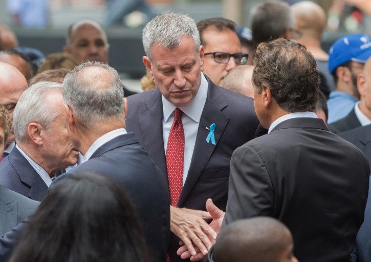 FILE - In this Sept. 11, 2015, file photo, New York City Mayor Bill de Blasio, center, and New York Gov. Andrew Cuomo shake hands during a ceremony at the World Trade Center site in New York.  AP