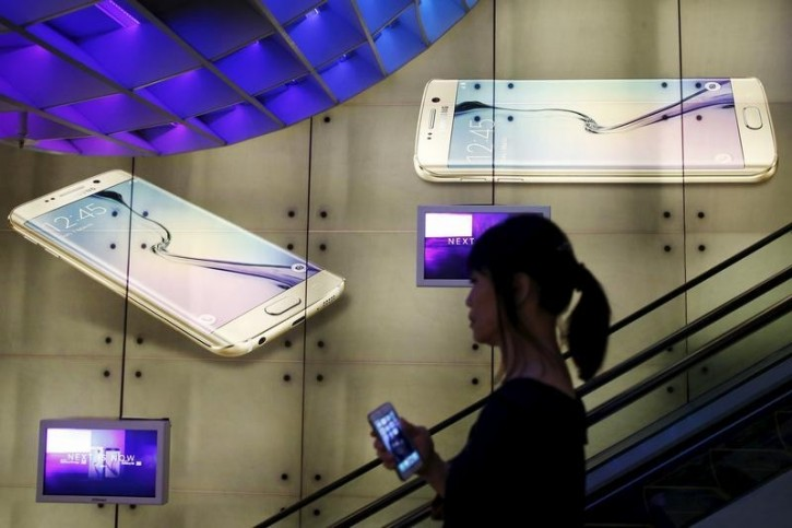 A woman holding an Apple iPhone passes a Samsung Galaxy S6 advertisement at a mall in Singapore April 24, 2015. REUTERS/Edgar Su  - RTX1AEBC