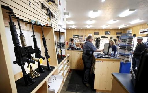 FILE - David Warren rings up customers sales next to assault rifles on display at the Ringmasters of Utah gun range and store, in Springville, Utah on December 18, 2015. REUTERS/George Frey