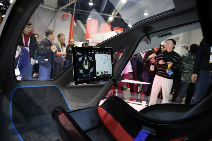 People crowd around the EHang 184 autonomous aerial vehicle at the EHang booth at CES International, Wednesday, Jan. 6, 2016, in Las Vegas. The drone is large enough to fit a human passenger. (AP Photo/John Locher)