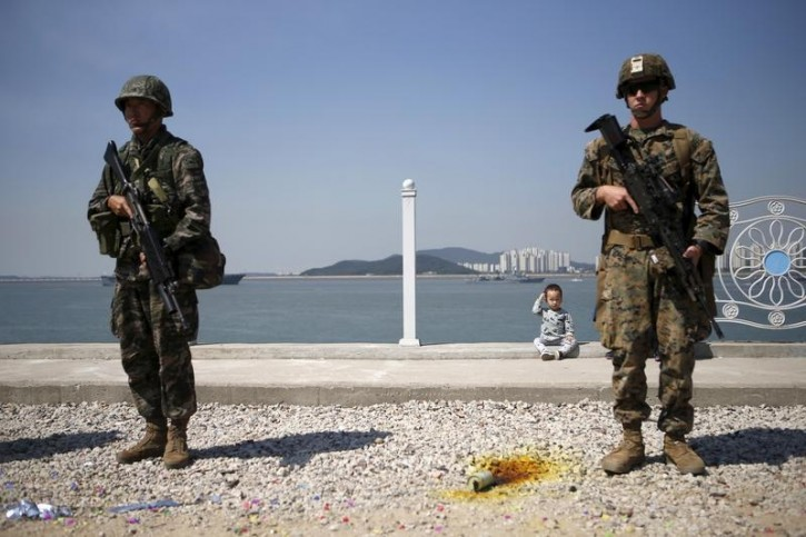 FILE - A boy sits between U.S. and South Korea marines during a ceremony to mark the 65th anniversary of Incheon Landing Operations conducted by the U.S.-led United Nations troop during the 1950-1953 Korean War, in Incheon, South Korea, September 15, 2015.   REUTERS/Kim Hong-Ji