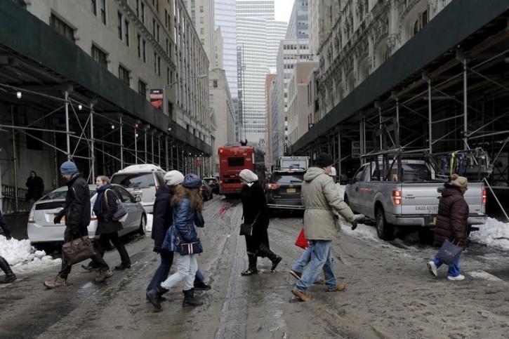 People cross slush and snow covered street in lower Manhattan in New York January 25, 2016. REUTERS/Brendan McDermid