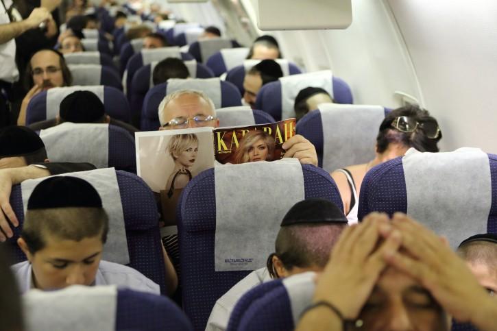 FILE Ilustration - A man seen reading a magazine among ultra orthodox Jewish travelers aborad ElAl flight. Flash90