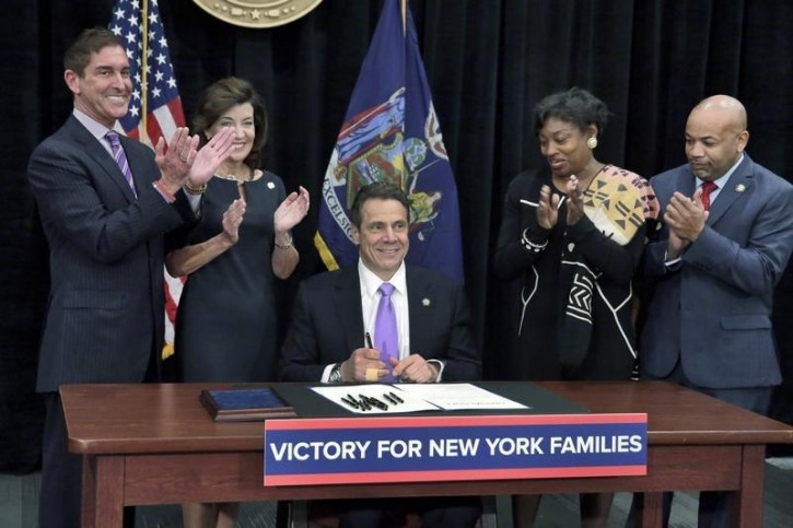 New York Gov. Andrew Cuomo (C) is applauded after he signed  a law that will gradually raise New York's minimum wage to $15, at the Javits Convention Center, in New York,  April 4, 2016. Standing, left to right, are New York state Sen. Jeffrey Klein, New York Lt. Gov. Kathy Hochul, New York state Sen. Andrea Stewart-Cousins, and New York state Assembly Speaker Carl Heastie. REUTERS/Richard Drew/Pool