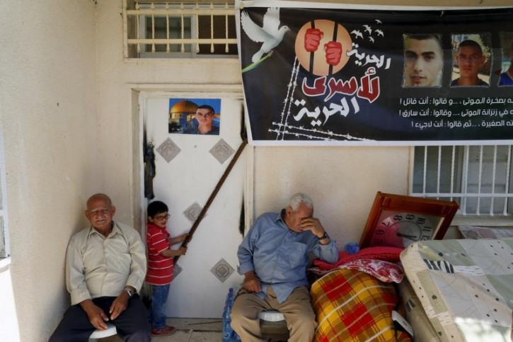 Family members of Palestinian Abed Mohammad Rabo Dawiyat sit at the entrance of their home after Israeli security forces sealed their house in Sur Baher, a village in the suburbs of Arab east Jerusalem, April 11, 2016. REUTERS