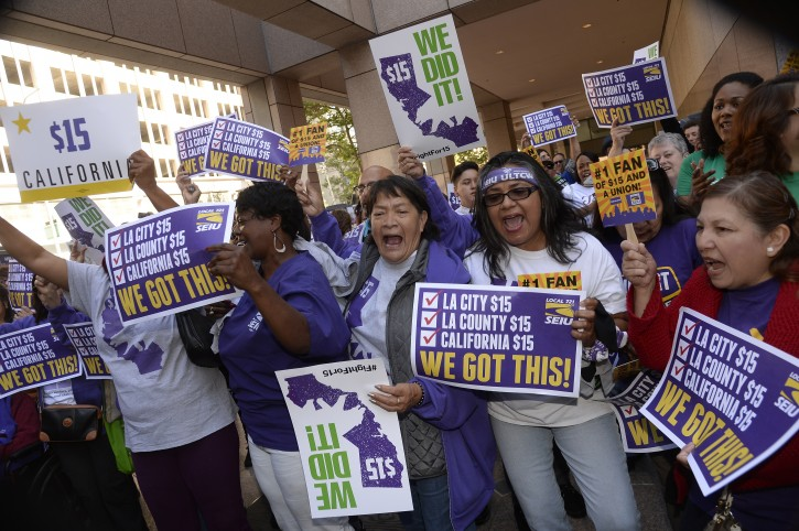 Supporters of the new minimum wage law celebrate after California Governor Jerry Brown signed landmark minimum wage legislation which makes California the  first state  in the nation  to commit to  raising the minimum wage to 15 US dollars an hour in Los Angeles, California, USA, 04 April 2016.   The SB3 law will gradually raise the minimum wage reaching 15 US dollars an hour in 2022.  EPA/MIKE NELSON