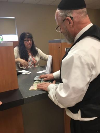 Joseph Waldman, owner of Simi's of London in Kiryas Joel returning the money to  teller Fran Keeshen on April 13, 2016