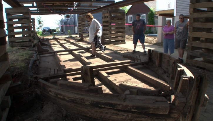 Eileen Scanlon, left, steps across a 44-foot wooden boat on Wednesday, May 25, 2016, underneath a home she rents in Highlands, N.J. The 19th-century boat, likely used to transport coal and other goods, sat undisturbed until workers began raising the home Wednesday to put it on pilings. (Thomas P. Costello/Asbury Park Press via AP)