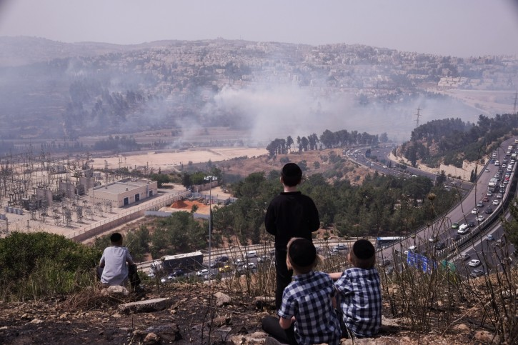 Ultra Orthodox Jews watch the smoke as a forest fire is spreading around Jerusalem's residential neighborhood of Ramot, on May 26, 2016. Photo by Yaniv Nadav/Flash90