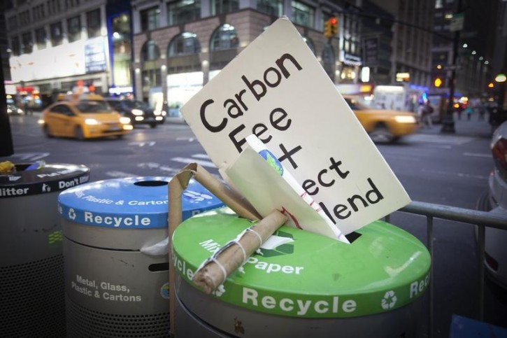 """FILE - A sign that had been carried during the """"People's Climate March"""" is discarded into the trash after the march in the Manhattan borough of New York September 21, 2014. Reuters"""