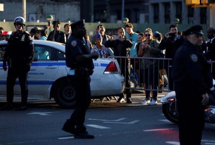 People watch U.S. President Barack Obama's motorcade as he travels between Democratic Party fundraisers in New York, U.S. June 8, 2016. REUTERS/Jonathan Ernst