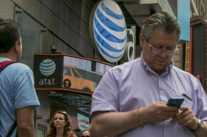 FILE - A man uses his phone outside the AT&T store in New York's Times Square, June 17, 2015. REUTERS/Brendan McDermid