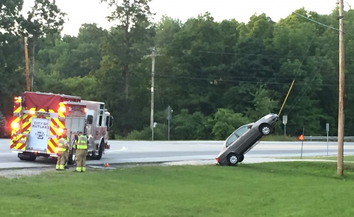 """This Wednesday, July 27, 2016, photo provided by G. Ray Ault shows a vehicle on wires attached to a utility pole in Mendon, Vt. Police in Vermont say the car ended up almost vertical when the driver swerved quickly in response to her GPS ordering her to """"turn around."""" (G. Ray Ault via AP)"""