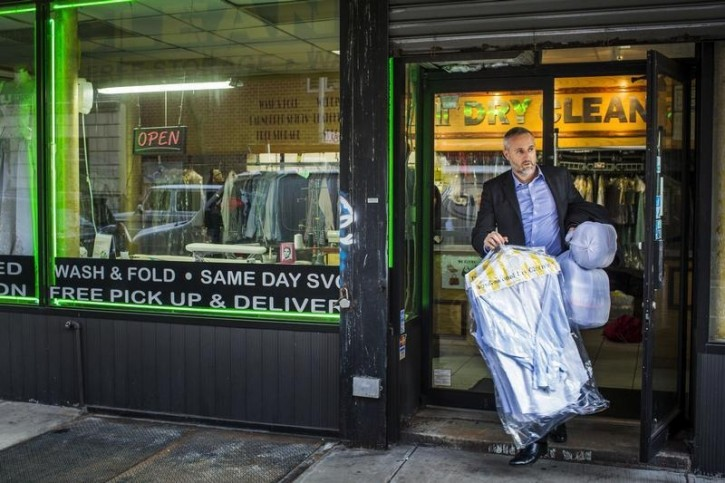 FILE - A man walks with dry cleaning out of a store in New York April 13, 2015. REUTERS/Lucas Jackson