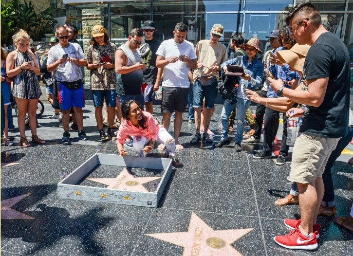 """This Tuesday, July 19, 2016 photo provided by Nick Stern shows a six-inch high, concrete-appearing 'wall,' created by an artist, surrounding the Hollywood Walk of Fame star of Donald Trump in Los Angeles. It appeared the day the former reality TV star and entrepreneur secured the Republican nomination for president. Tourists snapped photos of the wall, topped with razor wire and plastered with """"keep out"""" signs. The tiny wall was gone by Wednesday morning. (Nick Stern via AP)"""