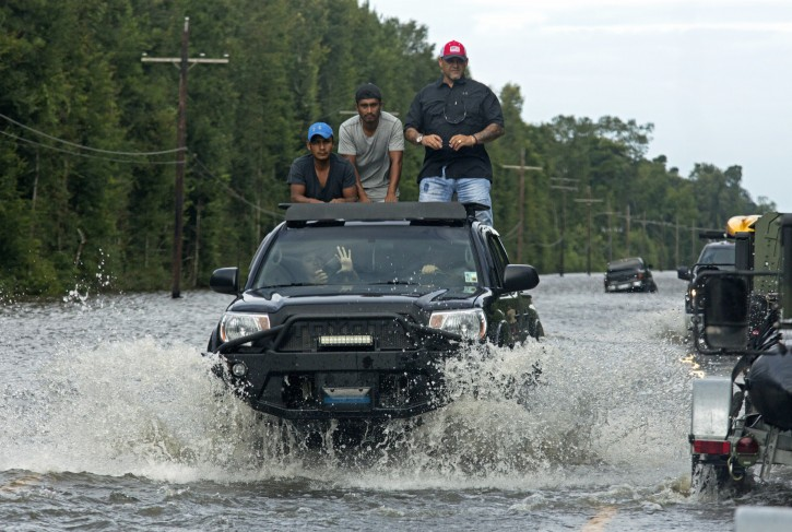 Motorists on Highway 190 drive through deep water through Holden, La., after heavy rains inundated the region, Sunday, Aug. 14, 2016. Louisiana Gov. John Bel Edwards said Sunday that at least 7,000 people have been rescued so far. (AP Photo/Max Becherer)