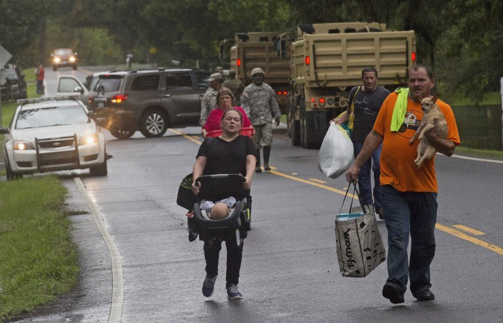 People arrive to be evacuated by members of the Louisiana Army National Guard near Walker, La., after heavy rains inundating the region, Sunday, Aug. 14, 2016. (AP Photo/Max Becherer)