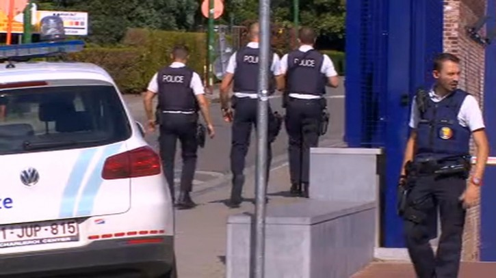 Police secure the area near to the scene of a machete attack on two police officers Saturday Aug. 6, 2016, outside the police station in Charleroi, Belgium. The attack happened Saturday at a checkpoint providing an additional layer of security outside the town police station. (RTL via AP)