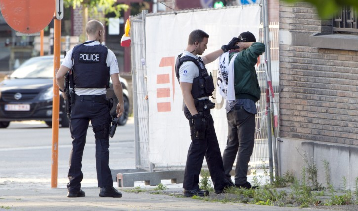 Police officers check identification of a man near the police headquarters in Charleroi, Belgium on Saturday, Aug. 6, 2016. A man attacked two police officers with a weapon near the headquarters on Saturday before being apprehended. (AP Photo/Virginia Mayo)