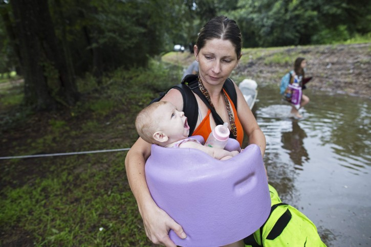 Danielle Blount carries her 3-month-old baby Ember to a truck from the Louisiana Army National Guard as they evacuate the area near Walker, La., after heavy rains inundated the region, Sunday, Aug. 14, 2016. (AP Photo/Max Becherer)