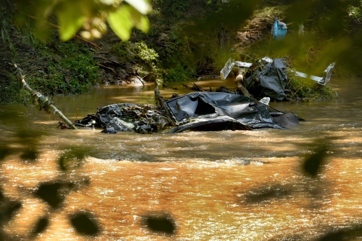 A submerged car is visible in the Patapsco River, seen from the Howard County side of Patapsco Valley State Park after the sidewalk caved in due to Saturday night's flooding in Ellicott City, Md., Sunday, July 31, 2016. Historic, low-lying Ellicott City, Maryland, was ravaged by floodwaters Saturday night, killing a few people and causing devastating damage to homes and businesses, officials said. (Amy Davis/The Baltimore Sun via AP)