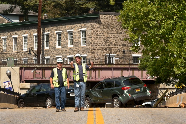 Crew members work near the railroad trestle at the end of historic Main Street, where flood damaged vehicles block the street after Saturday night's flooding in Ellicott City, Md., Sunday, July 31, 2016. Historic, low-lying Ellicott City, Maryland, was ravaged by floodwaters Saturday night, killing a few people and causing devastating damage to homes and businesses, officials said. (Amy Davis/The Baltimore Sun via AP)