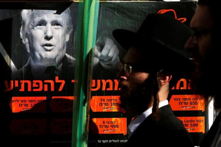 Ultra-Orthodox Jewish man walk next to a poster of Donald Trump in Jerusalem's Mea Shearim neighbourhood, October 13, 2016. REUTERS/Amir Cohen