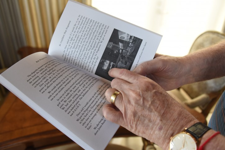 Bob Pergament at his home on Tuesday, Dec. 13, 2016 at St. Andrews Country Club in Boca Raton, Fla. Mr. Pergament reads from his book that he authored pointing to a photo that shows the news scroll at an undated time at Times Square showing an ad for Pergament Stores.
