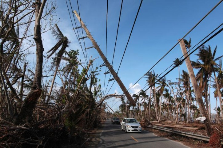 Cars drive under a partially collapsed utility pole, after the island was hit by Hurricane Maria in September, in Naguabo, Puerto Rico October 20, 2017. REUTERS/Alvin Baez