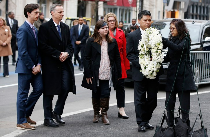 The father of Lingzhi Lu, Jun Lu, second from right, and her aunt Helen Zhao, right, place a wreath as the family of Martin Richard, from left, Henry, Bill, Jane and Denise look on during a ceremony at the site where Matin Richard and Lingzhi Lu were killed in the second explosion at the 2013 Boston Marathon, Sunday, April 15, 2018, in Boston. (AP Photo/Michael Dwyer)