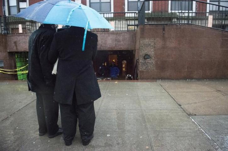 FILE - Men stand under an umbrella in Brooklyn December 9, 2014. REUTERS