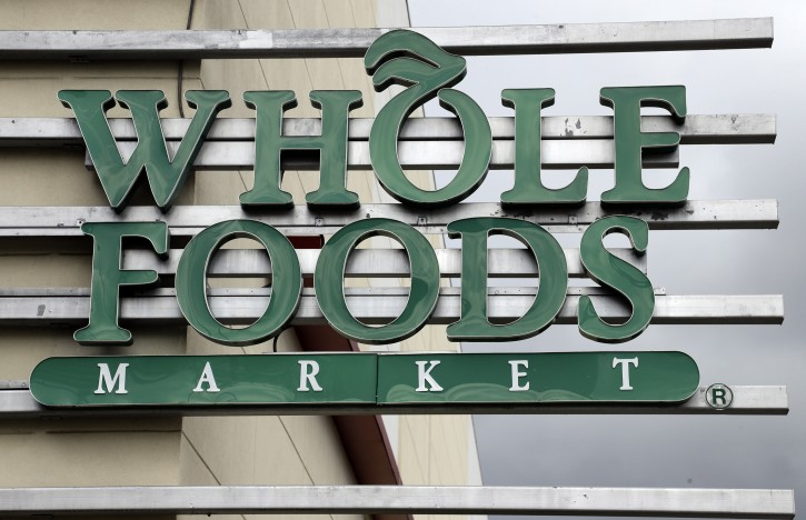 FILE - In this Monday, Aug. 28, 2017, file photo, a sign at a Whole Foods Market greets shoppers in Tampa, Fla. Amazon is bringing its Prime membership to Whole Foods, giving members special discounts and deals at the organic grocer. T(AP Photo/Chris O'Meara, File)