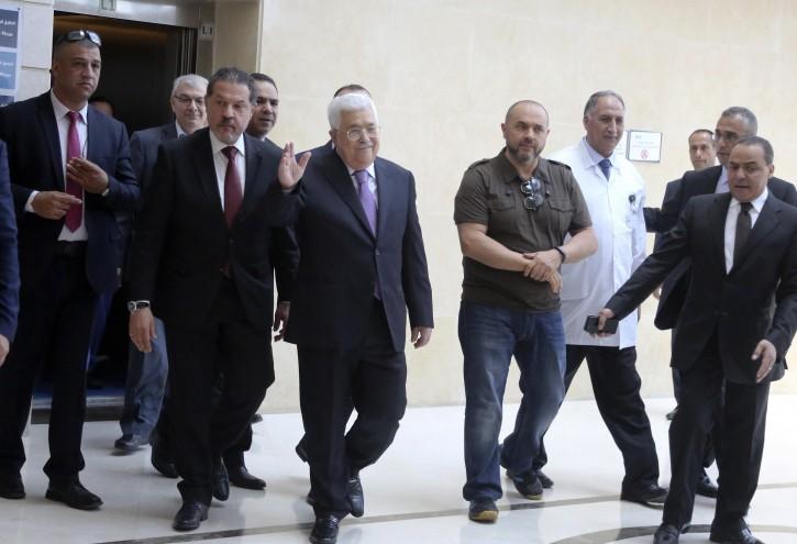 Palestinian President Mahmoud Abbas (C) walks with his sons, Yasser Abbas (C-L) and Tarik Abbas (C-R) as he leaves the hospital, in Ramallah, 28 May 2018.EPA