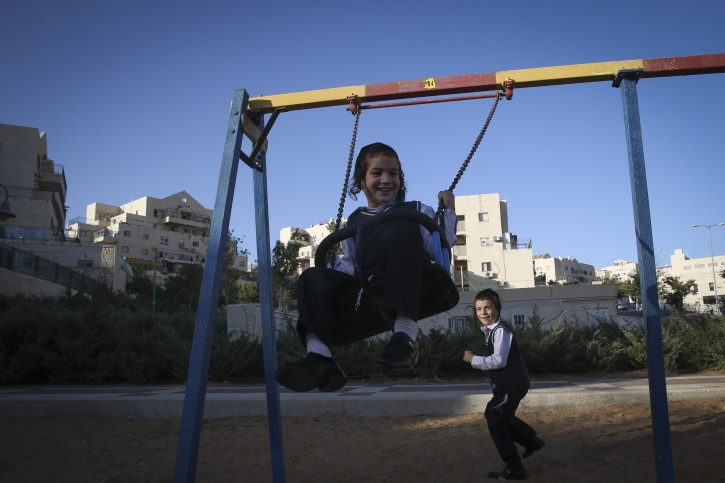 FILE - Young boys play on a swing in a park on September 17, 2014. Photo by Nati Shohat/Flash90