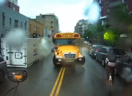 Image taken from video shows one school bus driver using his bus to stop a cyclist who had just passed a school bus whose red lights were flashing.