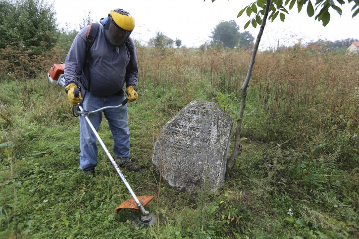 In this photo taken on Aug. 29, 2018, Steven Reece, an ordained Southern Baptist minister who lives near Atlanta cleans an old Jewish cemetery in Rohatyn, the site of a Jewish Heritage project, close to Lviv, Ukraine, Aug. 29, 2018. For years now, Reece, an ordained Southern Baptist minister from Texas, has been cleaning Jewish cemeteries and erecting memorial plaques at mass grave sites in Poland, and recently Ukraine. (AP Photo/Yevheniy Kravs)