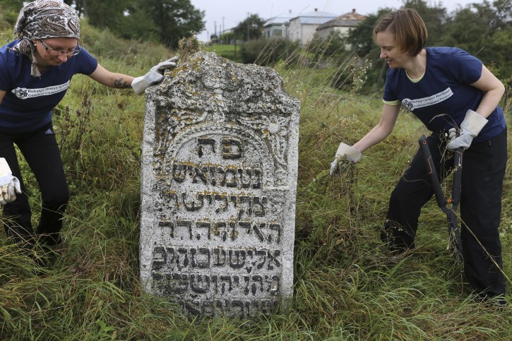 In this photo taken on Aug. 29, 2018, volunteers clean an old Jewish cemetery in Rohatyn, the site of a Jewish Heritage project, close to Lviv, Ukraine. (AP Photo/Yevheniy Kravs)