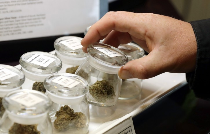In this Sept. 24, 2018 photo, different strains of marijuana are displayed for sale at the Warmland Centre, a medical marijuana dispensary in Mill Bay, British Columbia on Vancouver Island in Canada. On Oct. 17, 2018, Canada will become the second and largest country with a legal national marijuana marketplace, forcing many dispensaries, including Warmland, to close temporarily until they receive licenses under the new recreational system. (AP Photo/Ted S. Warren)